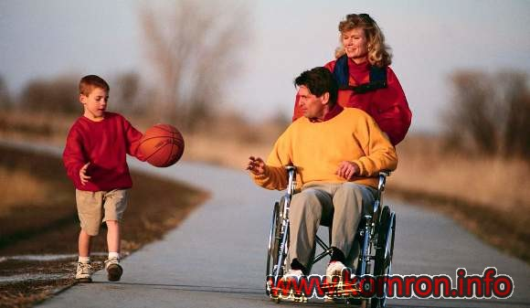 A woman pushes her husband in a wheelchair while their son bounces a basketball. --- Image by © Royalty-Free/Corbis